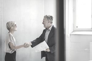 Mature businessman and businesswoman shaking hands in new office