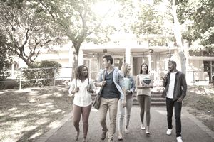 Full length shot of a group of college students enjoying walking together between classes on campus