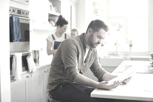 man sitting at counter paying bills while wife and kid are behind him