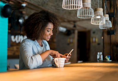 Woman looking at social media at a cafe on her cell phone while having a cup of coffee