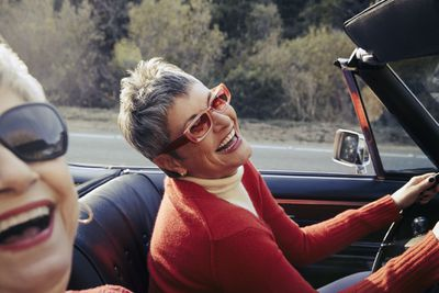Mature woman driving convertible car laughs with passenger