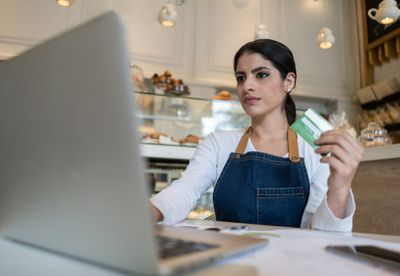 A bakery owner holds a business credit card in her hand as she prepares to place an order on her laptop