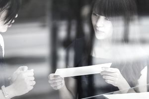 Two women look at a letter while standing behind a window