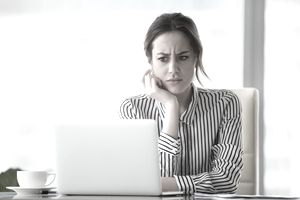 Young woman in black and white striped shirt stares suspiciously at a laptop screen.