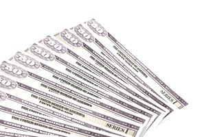 Closeup of $50 Series I savings bonds spread out on a white surface