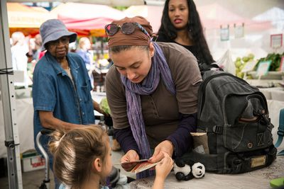 A white woman and her daughter shopping with EBT coupons, also known as food stamps, represent the largest racial group that benefits from SNAP in the U.S.