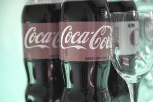 Coca-Cola bottles with a glass.