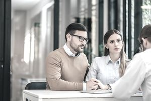 Man and woman holding hands and looking concerned in an office