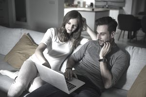 Man and woman sitting on a sofa working on a laptop