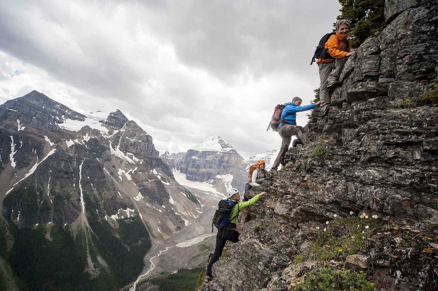 Four Mountaineers Ascend Cliff Above Mountains