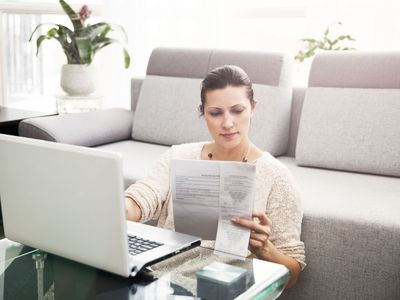 Woman Sitting on the Floor at a Laptop, Studying Papers