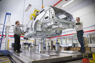 Two factory workers manufacturing a car