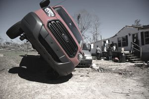 A cargo truck leans on another vehicle after the area was destroyed by a tornado touchdown