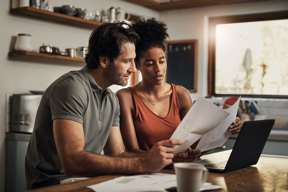 Couple reviewing financial documents in their kitchen.
