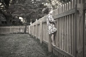 Girl peeking over a fence between properties