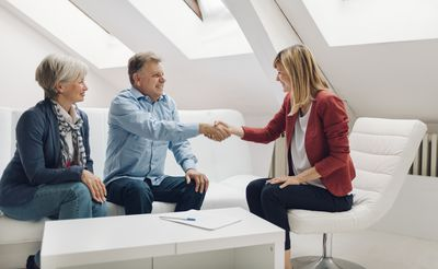 Mature couple meeting with a financial advisor in a casual white office