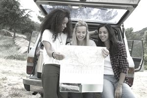 Young women looking at map at back of car