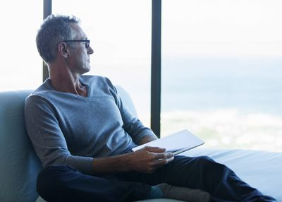 Concerned older man with tablet looking out window at expansive skyline