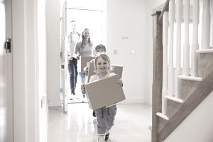 a family carrying boxes into a house