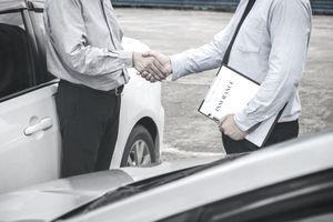 Two Men (Heads Not Shown) Shaking Hands Near Two Cars