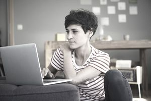 person in striped shirt sitting on floor while working on computer