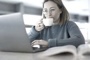 A woman drinks tea at her computer.