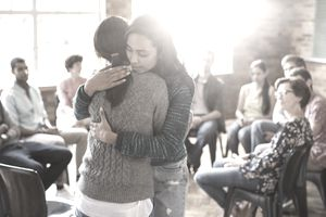 two women hugging in a mental health support group