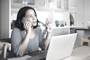 A woman holds a phone to her ear while chewing on her glasses and gazing past her laptop, looking concerned