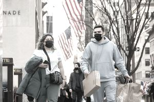 A man and woman wearing masks can carrying shopping bags