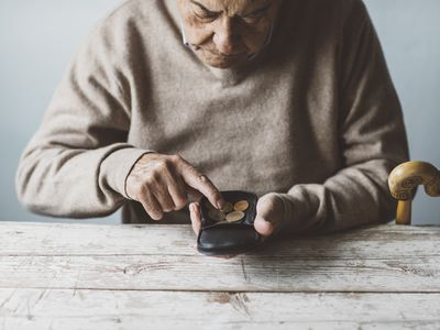An elderly man counting change