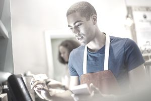 Young man wearing apron uses touch-screen computer to place order