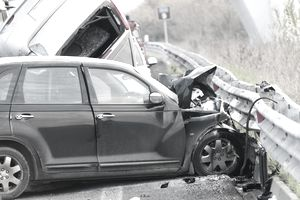 Two smashed cars by a guardrail after a collision.