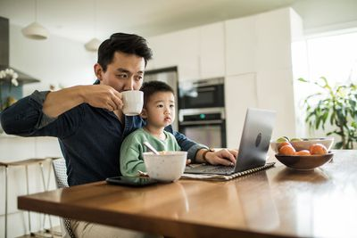 Father multi-tasking with young son at kitchen table