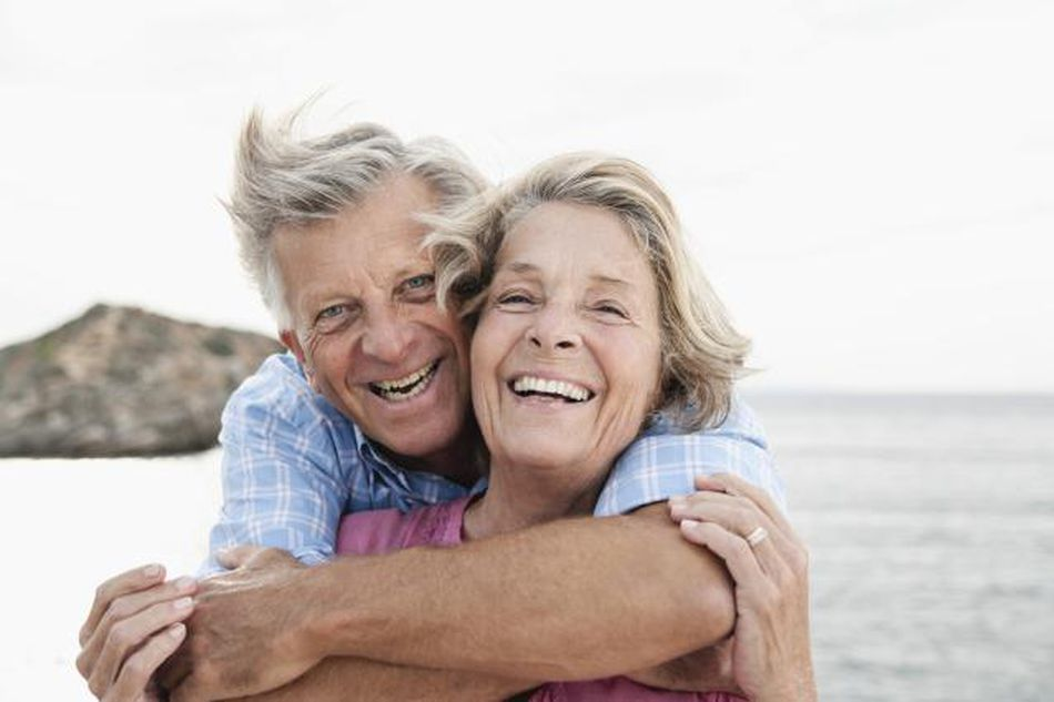 Happy older couple hugging next to the ocean on a windswept beach.