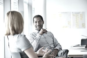 Older executive speaking with younger employee in a modern office
