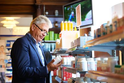 An older man stands in a drugstore and reads the label on a bottle of pills.