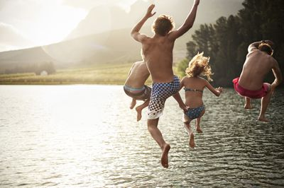 four people leaping mid-air over a body of water