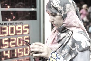 A woman checks her cell phone in front of currency exchange kiosk
