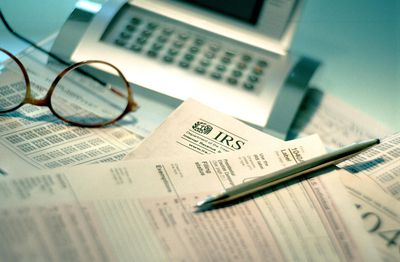 Calculator and tax forms laying on a desk with a pair of glasses and a pen.