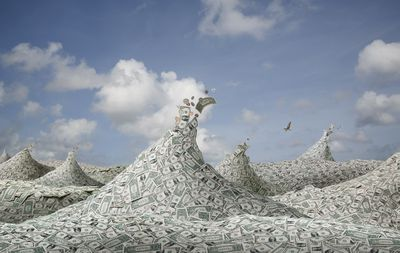 Waves made of cash, representing fund flows.