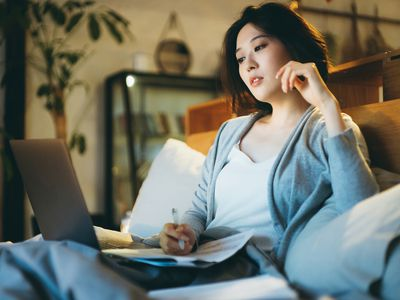 Busy young Asian woman sitting on the bed, working from home using laptop and handling paperworks till late in the evening at home