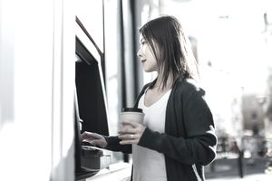 Woman at ATM holds her bank card and coffee cup