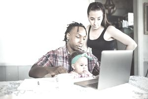 African American dad works on a computer with his infant daughter with mom.