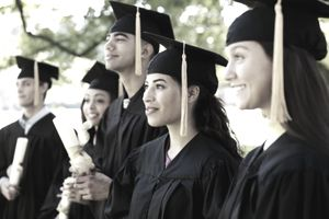 group of recent college graduates in cap and gown with diplomas