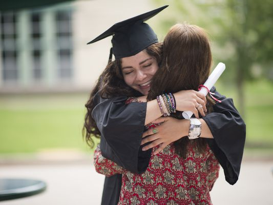 college graduate in cap and gown hugs her mom