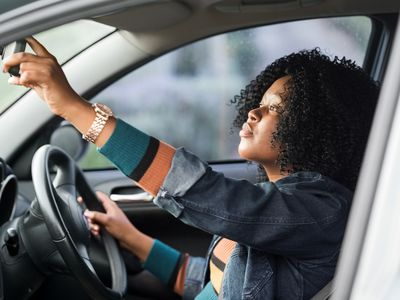 A woman is adjusting the rear-view mirror before she drives.