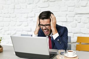 Man working at laptop expressing frustration