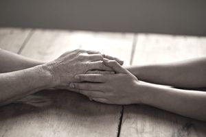 A cropped shot of a woman holding a loved one's hand in support.