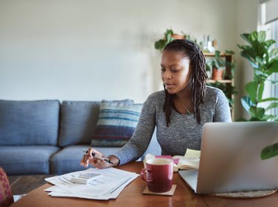 A woman sits at a home table calculating taxes with a piles of paper and a laptop