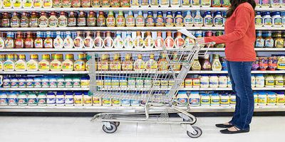 Woman grocery shopping with a list to cut back on her expenses